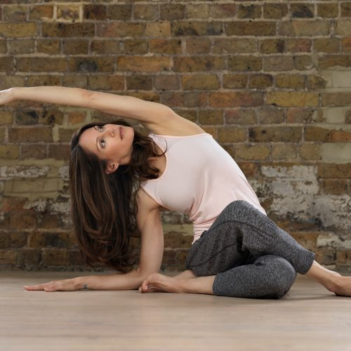 A photograph of Janine Tandy, performing a yoga position, against a brick wall.