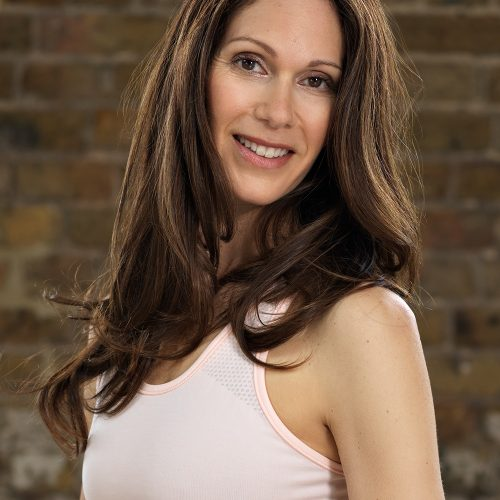 A photograph of Janine Tandy, wearing a light pink sports top, posing for a headshot against a brick wall