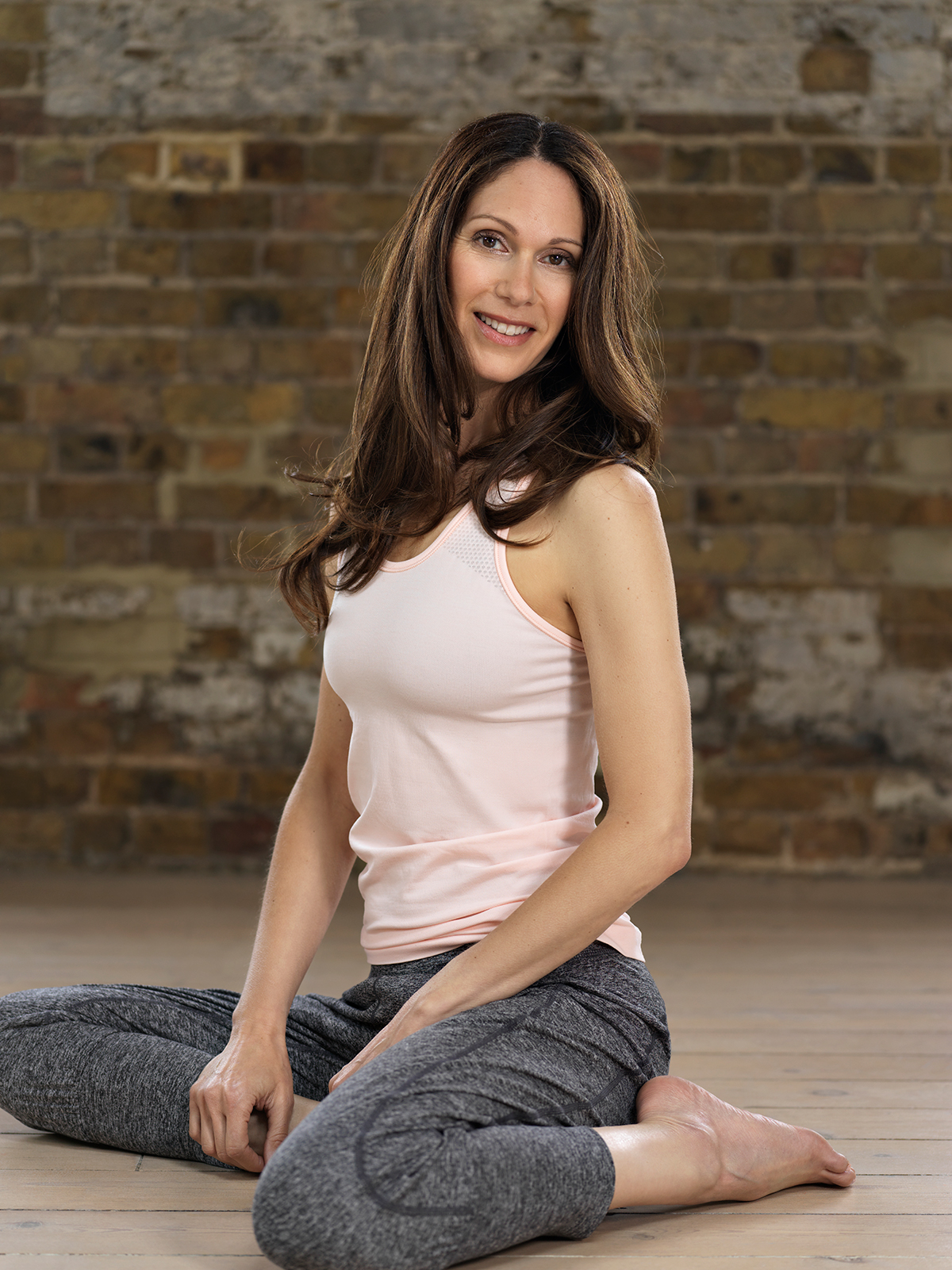 A photograph of Janine Tandy, against a brick wall.