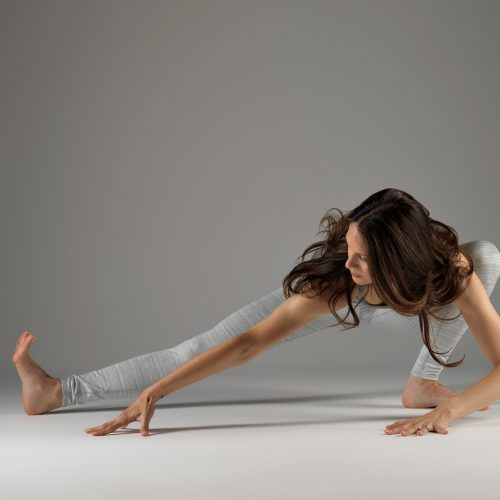 A photograph of Janine Tandy performing a yoga pose, with her right left extended, against a grey background