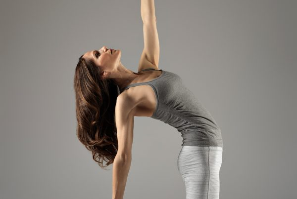 A photograph of Janine Tandy performing a yoga pose, with her left arm raised, against a grey background