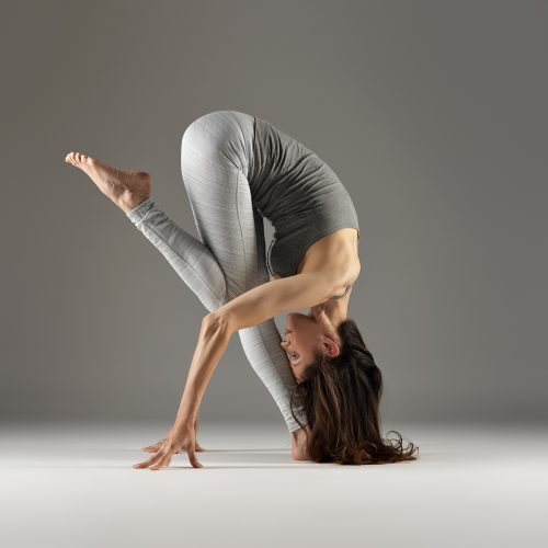A photograph of Janine Tandy performing a yoga pose against a grey background