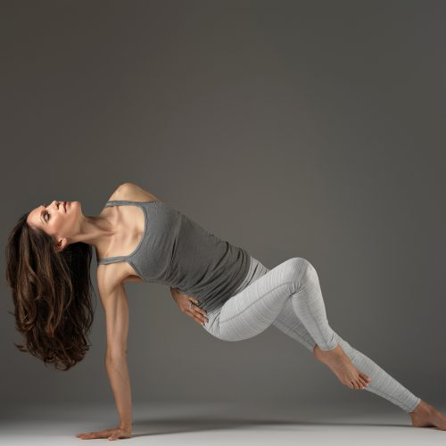 A photograph of Janine Tandy, performing a yoga position, against a grey background